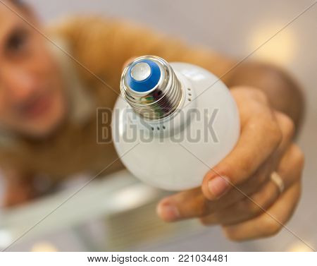 A closeup of hands putting in and twists a bulb standing on a ladder. Stock photo