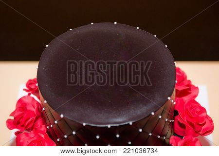 Chocolate birthday cake with red roses, copy space on the top of the cake
