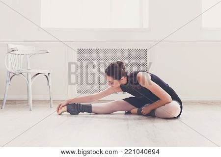 Beautiful graceful ballerina in black leotard practice legs and back stretching in class room background. Ballet class training, copy space