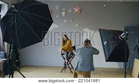 Professional photographer man taking photo of beautiful model girl with digital camera in studio indoors