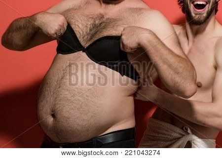 male hairy belly with lingerie. gay and lgbt. couple of naked guys try on female brassiere. transgender and bisexuality. fat man in female bra.