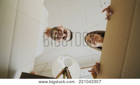 Young happy couple opening cardboard box and looking inside and closing it checking after relocation in new house indoors