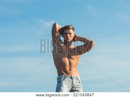 Macho show muscular torso in jeans on blue sky. Sportsman with bare torso, six pack, ab, biceps, triceps, muscles. Sport, bodybuilding, fitness, health concept.