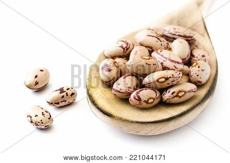 Raw pinto beans on wooden spoon isolated on white background