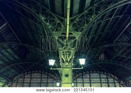 Fragment of roof construction the city railway station Vitebsky. Vaulted structure of steel roof frame truss windows. Railroad station platform in St Petersburg, Russia. Vintage architecture at night.