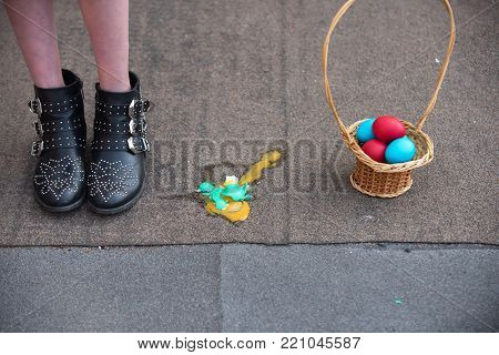 Easter eggs and female feet in boots on asphalt background. Wicker basket with colored eggs. Broken eggshell with yellow yolk spilt on paving. Fertility and rebirth concept. Easter holiday celebration