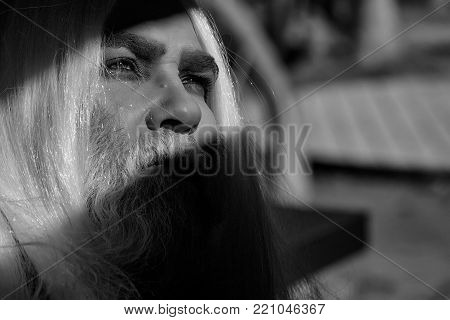 Druid old man with long silver beard and hair with bright light on face with wrinkles on blurred background