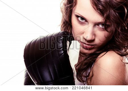 Martial arts or emancipation idea concept. Sport boxer woman in black gloves. Fitness girl training kick boxing showing her power domination. Isolated on white background.