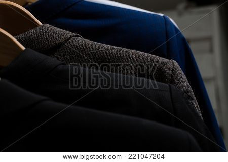 Collection of formal jackets on hangers on blurred background. Business fashion, style concept.