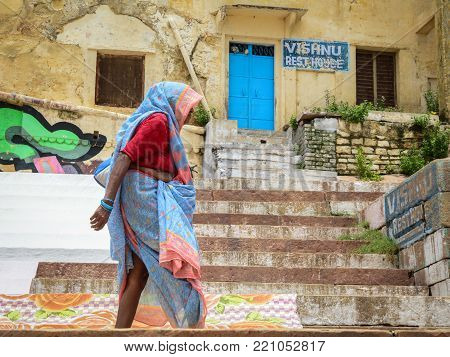 Varanasi, India - Jul 12, 2015. An old woman walking on street in Varanasi, India. Varanasi is the holiest of the seven sacred cities (Sapta Puri) in Buddhism, Hinduism and Jainism.