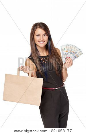 Shopping concept. Smiling woman holding paper shopping bag with blank copy space for text and cash US dollars, over white background
