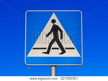 Crosswalk road sign against blue ske at winter