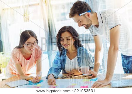 Productive cooperation. Happy positive young woman sitting together with her colleagues and pointing at the sticky note while enjoying their cooperation