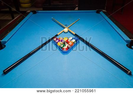 Billiards balls and cue on billiards table