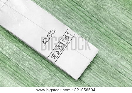 Fabric composition and washing instructions clothes label on green textile background