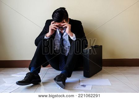 Close up of stressed young Asian businessman with glasses raise hands to touch his head and sit on floor. Feeling bad and headache against job after getting lay off or fired in office.