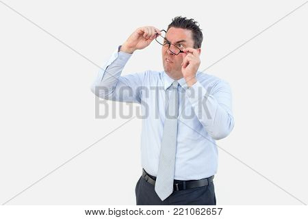 Closeup portrait of confused funny middle-aged business man taking off glasses. Misunderstanding concept. Isolated front view on white background.