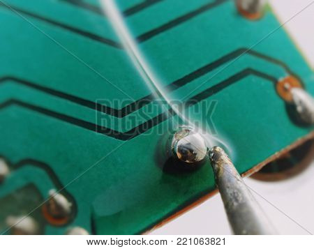soldering contact on a printed circuit board, isolated image on a white background, macro shooting, smoke from a soldering tip.