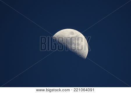 First quarter moon around dusk with a dark blue sky caused by blue hour