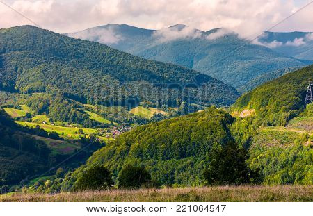 village in the valley of Carpathian mountains. lovely countryside scenery in early autumn with clouds rising from the forest on the distant ridge