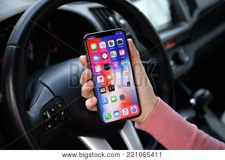 Alushta, Russia - December 16, 2017: Woman hand holding iPhone X with IOS 11 on the screen in the car. iPhone 10 was created and developed by the Apple inc.