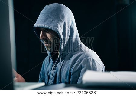 criminal mysterious man hides his face under the hood, doing something illegal