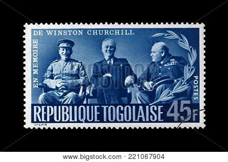 TOGO - CIRCA 1965: canceled stamp printed in Togo shows Stalin, Roosevelt and Churchill at Yalta Crimean conference during World War II, circa 1965. Vintage post stamp isolated on black background.