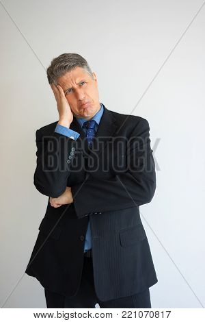 Closeup portrait of middle aged Caucasian man posing with comical thoughtful facial expression and head on hand. Executive making decision and grimacing. Decision making or fun concept