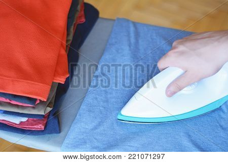 Top view of man ironing blue shirt on ironing board with stack of ironed shirts. Housework concept