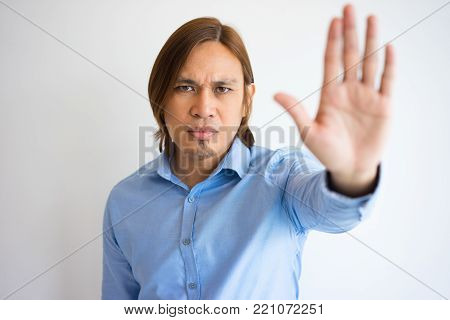 Portrait of serious young Asian man with hand raised in stop gesture. Freelancer warning colleagues of making typical mistakes. Stop and warning concept