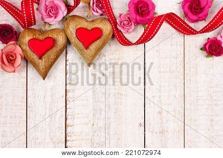 Two Valentines Day wood hearts with roses and ribbon top border against a rustic white wood background with copy space.