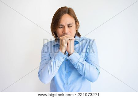 Portrait of tense young Asian man with closed eyes covering mouth with clasped hands and praying. Young businessman pleading for help. Business and crisis concept
