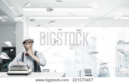 Young man writer in hat and eyeglasses using typing machine while sitting at the table indoors among flying paper planes and with office view on background.