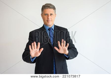 Portrait of serious CEO with both hands raised in stop gesture. Confident middle aged boss admonishing young colleagues of making typical mistakes. Leadership and warning concept.