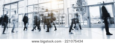 crowd blurred business people walking in at a trade show floor, banner size. ideal for websites and magazines layouts
