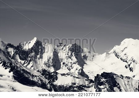 Black and white winter snowy mountains in cold sun day. Caucasus Mountains, region Dombay.