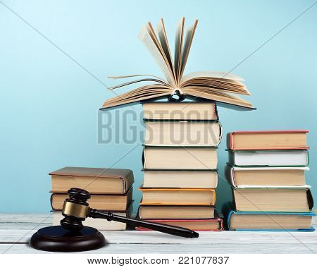 Law concept open book with wooden judges gavel on table in a courtroom or law enforcement office, blue background. Copy space for text
