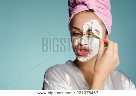 a young girl with a pink towel on her head takes off the white mask from her face