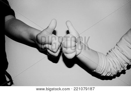 kids showing two thumbs up on b/w background