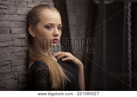 Beautiful Fashion Model Wearing Black Dress In Studio On Background Lighted With Green. Aggressove L