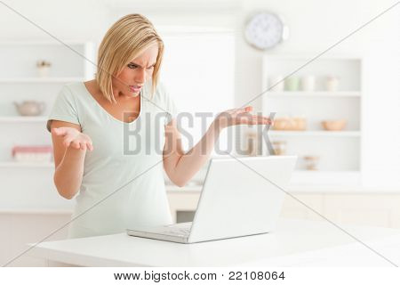 Woman looking at notebook in the kitchen without having any clue what to do