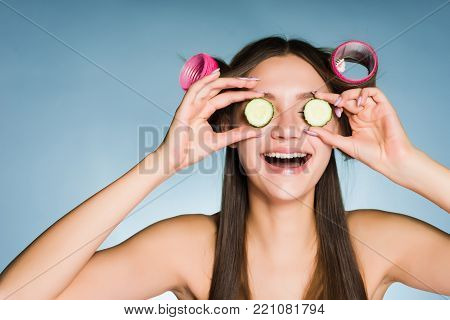 laughing young girl holding pieces of cucumber near the eyes, on the head of curlers