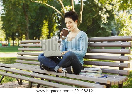 Young smiling woman sitting outdoors on bench with laptop, typing, surfing internet, preparing for exams. Technology, communication, education and remote working concept, copy space