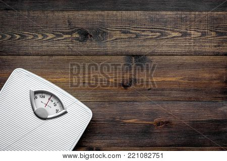 Lose weight concept. Scale on dark wooden background top view.
