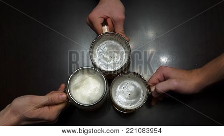 Cheers. Top View Of People Holding Mugs With Beer. Top Down Shot Of Three Pint Sized Beer Mugs On A