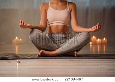 Close up of fit body of young woman doing yoga. She is sitting in lotus position on mat. Relaxation concept