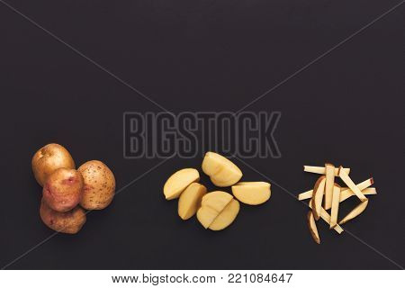 Whole and cut potato isolated on black background. Stages of cutting vegetable. Organic harvest and cooking ingredients concept, top view, copy space