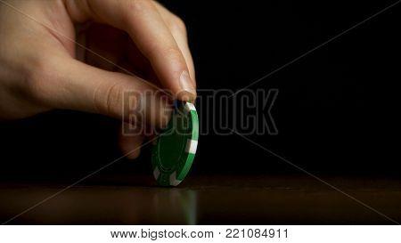 Rotation of poker chips on the table isolated on black background. Poker chips shaffling. Poker chip spinning on the table isolated on dark background.