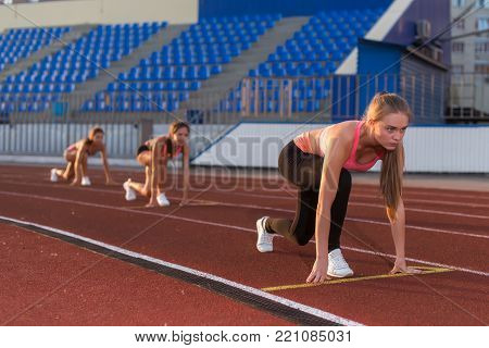 Women sprinters at starting position ready for race on racetrack poster