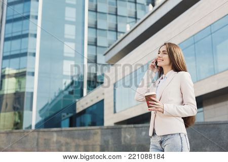 Happy businesswoman talking on smartphone outdoors. Caucasian executive having conversation, drinking take away coffee outdoors at modern office center in urban area cityscape